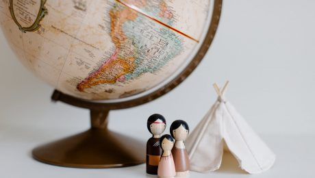 retro globe with handmade toys against gray background in room