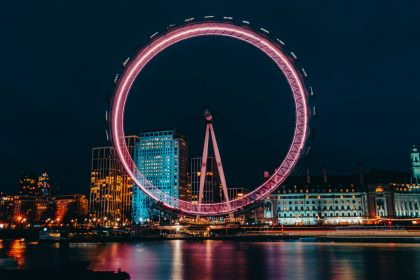 luminous ferris wheel in modern city district on river bank at night